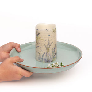 hands holding decorative led candle on plate