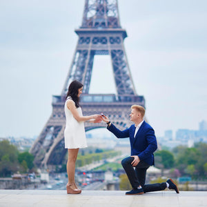 man proposing to woman in front of eiffel tower