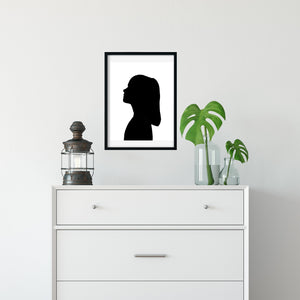 framed silhouette print hanging above drawer unit