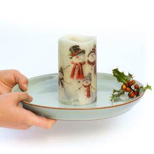 hands holding decorated led candle on plate