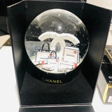 THERE'S A NO. 5 MINIATURE CHANEL PERFUME IN THE GLOBE ALONG WITH SIGNATURE WHITE BAGS, AND GORGEOUS CAMELLIAS ON THE BOTTOM.