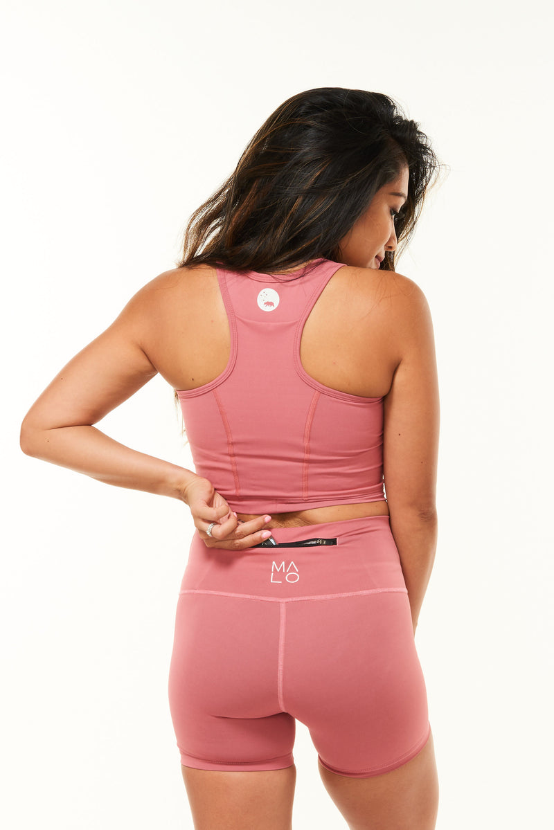 Model placing keys in the back pocket of pink running shorts. Workout shorts that hold your belongings