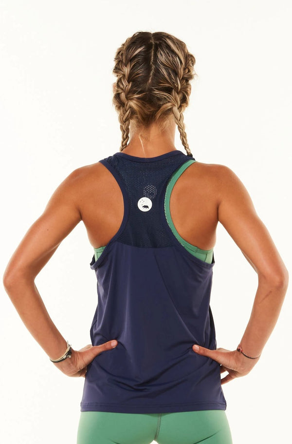 Back view Endure Tank. Navy sleeveless top with reflective logo. Women's tank top with mesh panel.