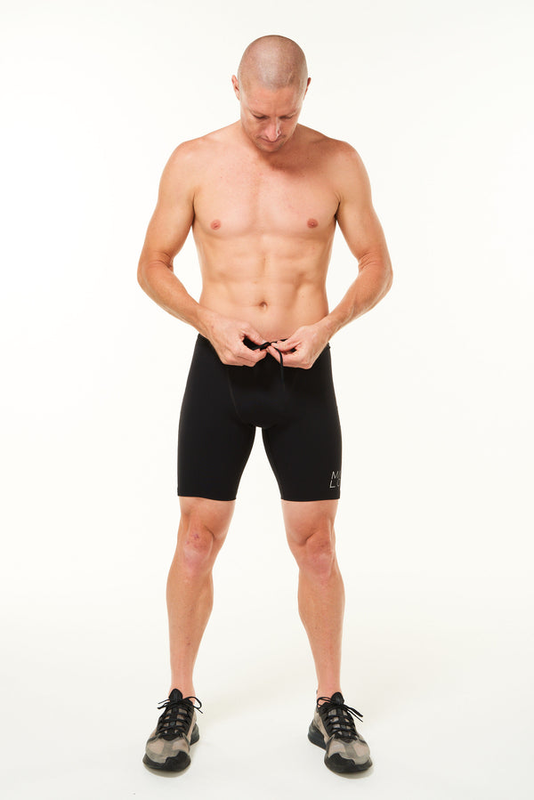 Model tying drawsting of Sprinter Shorts. Men's black running shorts. with adjustable waist.