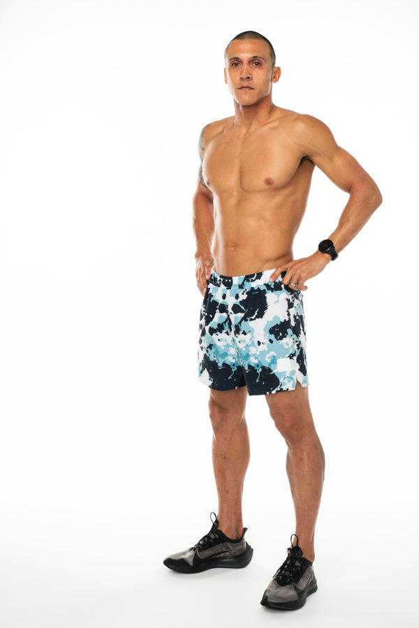 Left view men's Noosa Run Short. Mid-thigh camo run shorts with reflective logo and stripe on left thigh.