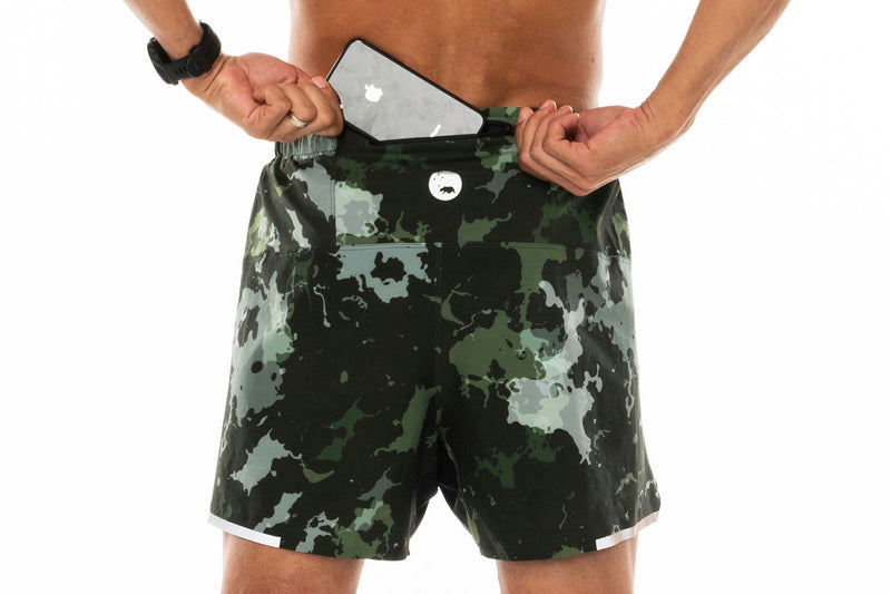 Model placing phone in back pocket of Moss Camo Noosa Run Short. Lined running shorts with pockets