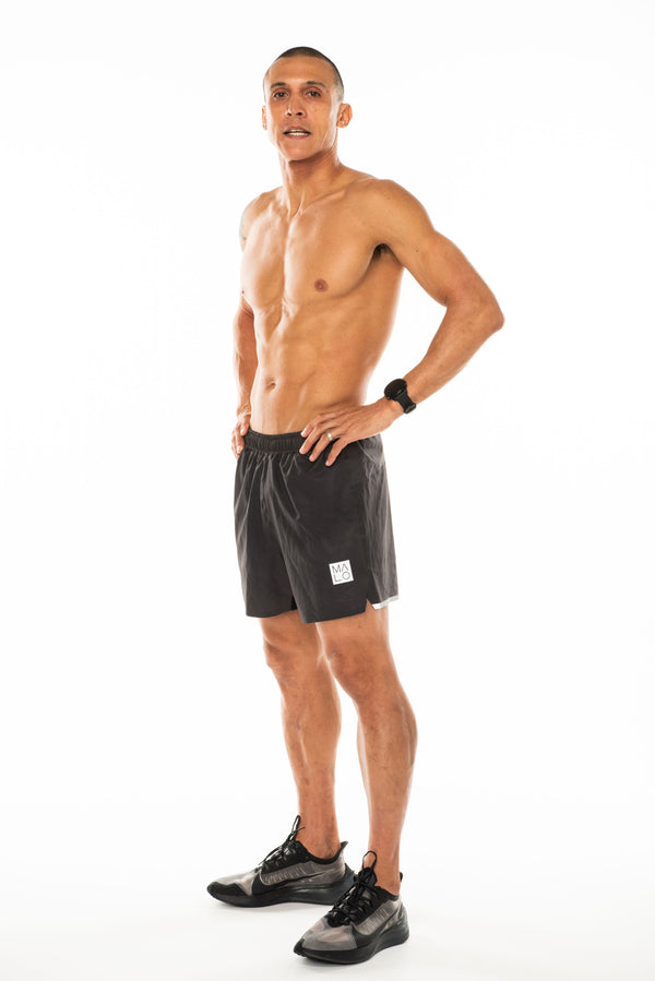 Left view men's Noosa Run Short. Mid-thigh gray run shorts with reflective logo and stripe on left thigh.