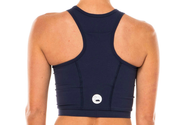 Back view women's Navy Core Crop. Navy form-fitting athletic top with reflective logo.