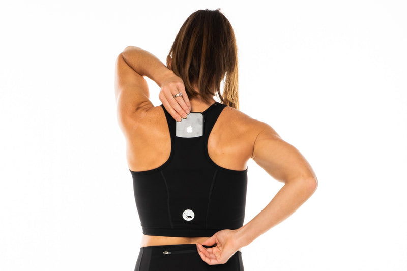 Model placing phone in back pocket of Black Core Crop. Women's running top with pockets.