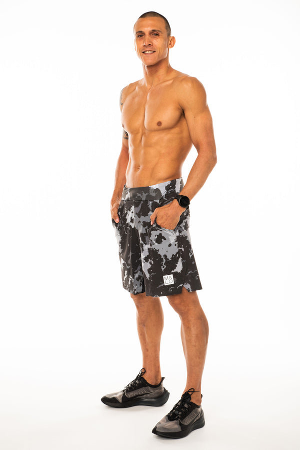 Left view model wearing Arvo Shorts with hands in pockets. Camo running shorts with reflective logo on left thigh.