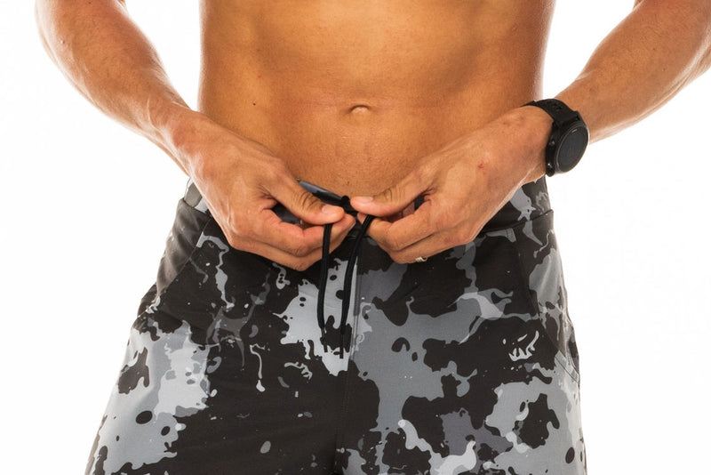 Model tieing drawstring in Arvo Shorts. Camo workout shorts with comfortable and adjustable waistline.