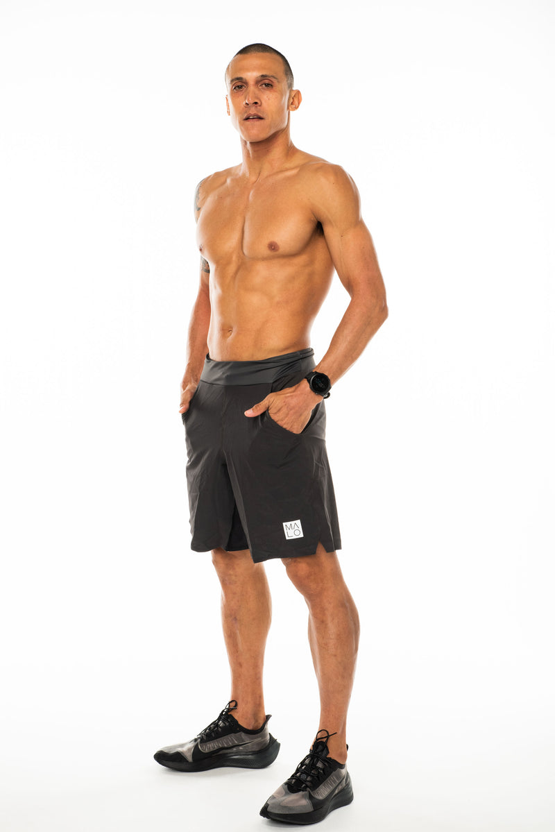 Model wearing Arvo Shorts. Above the knee grey athleisure shorts. Workout shorts with pockets.