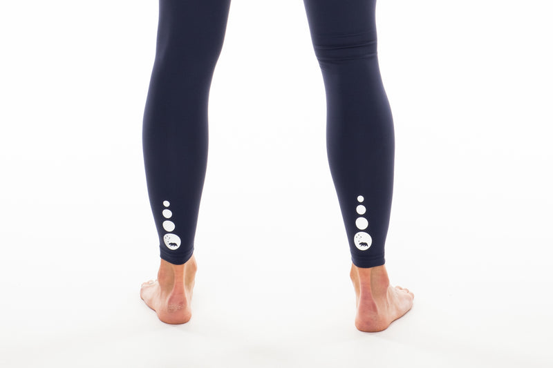 Close back view Hi Rise Luxe Leggings. Reflective logo by leg cuff.