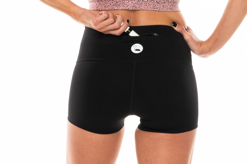 Model placing keys in back pocket of PR Shorts. Black workout shorts with zipper pocket in waistband.