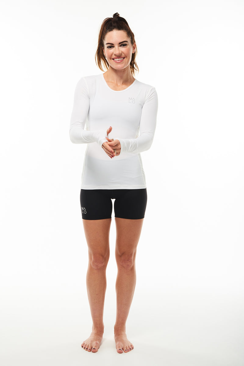 Women's white long sleeve running shirt. Performance tee with thumbholes to keep in warmth.