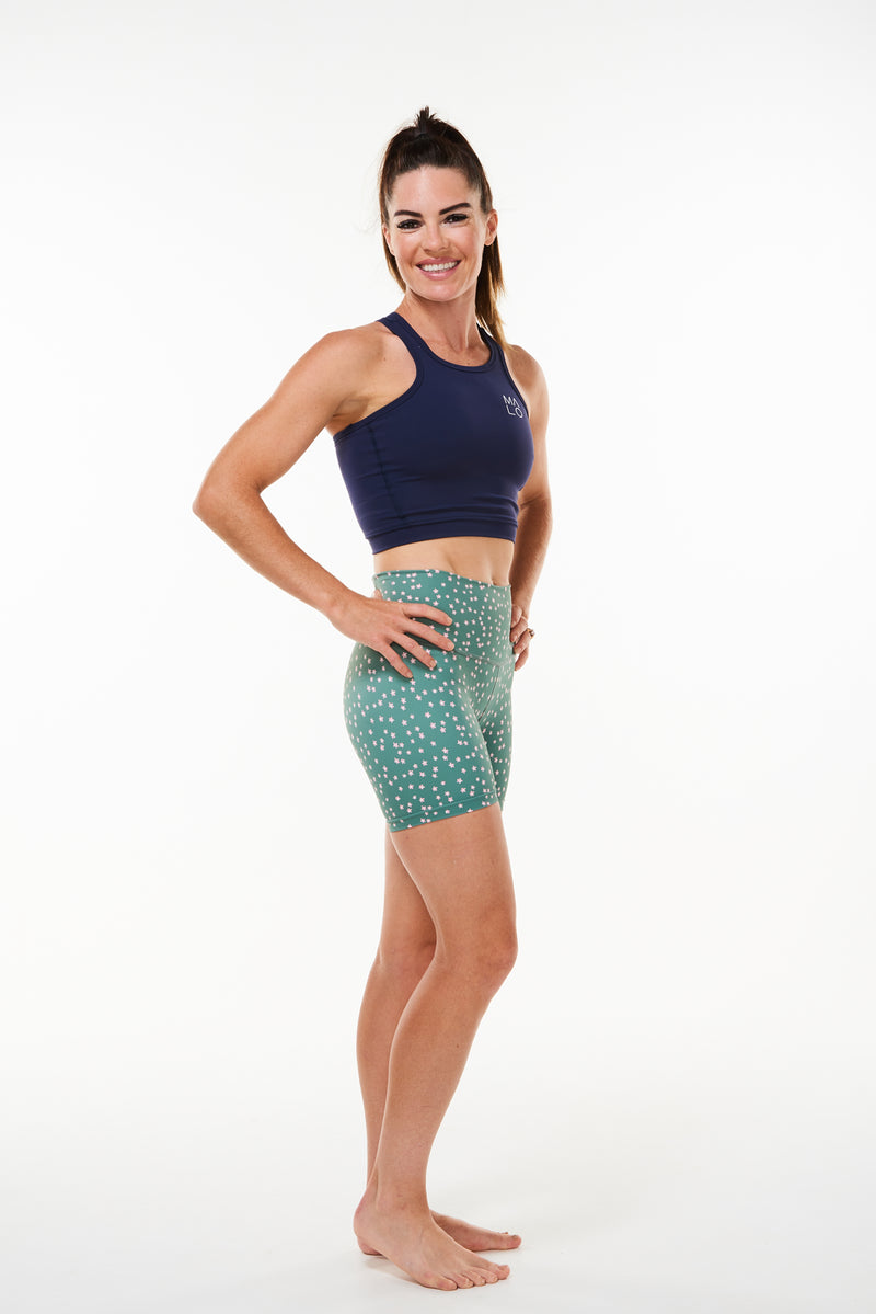 Right view model wearing green athleisure shorts with daisy print. Mid-thigh running shorts that are quick drying and breathable.