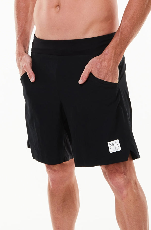 Left view model wearing Arvo Shorts with hands in pockets. Black running shorts with reflective logo on left thigh.