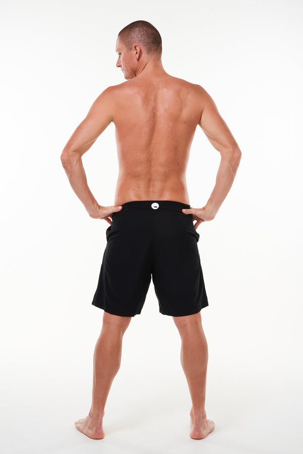 Back view of Arvo Shorts. Lined above the knee black workout shorts with reflective logo on waistline.