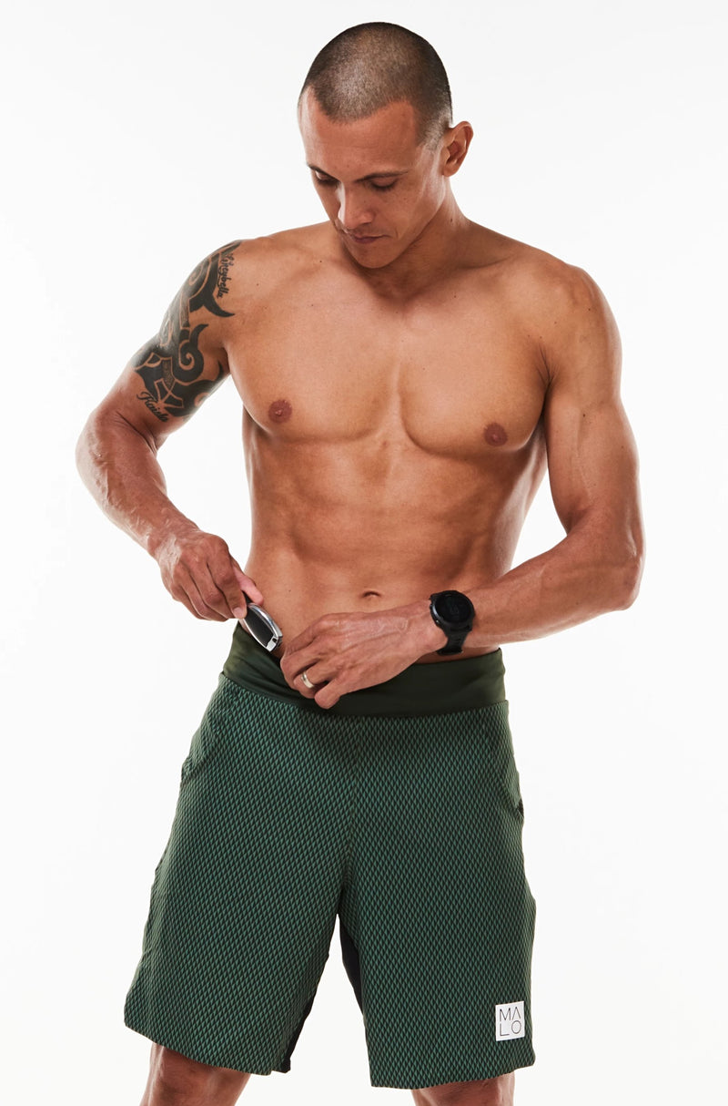 Model placing keys in small waistline pocket of Arvo Shorts. Green workout shorts with pockets.