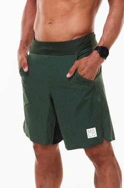 Left view model wearing Arvo Shorts with hands in pockets. Green running shorts with reflective logo on left thigh.