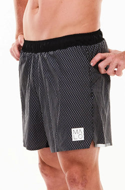 Left view men's Noosa Run Short. Black run shorts with reflective logo and stripe on left thigh.
