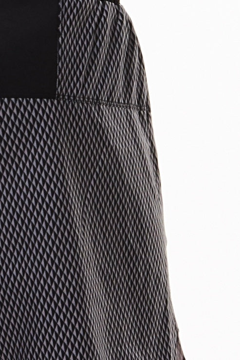 Close view men's Black Reflect Noosa Run Short fabric. Black and grey diamond pattern fabric.