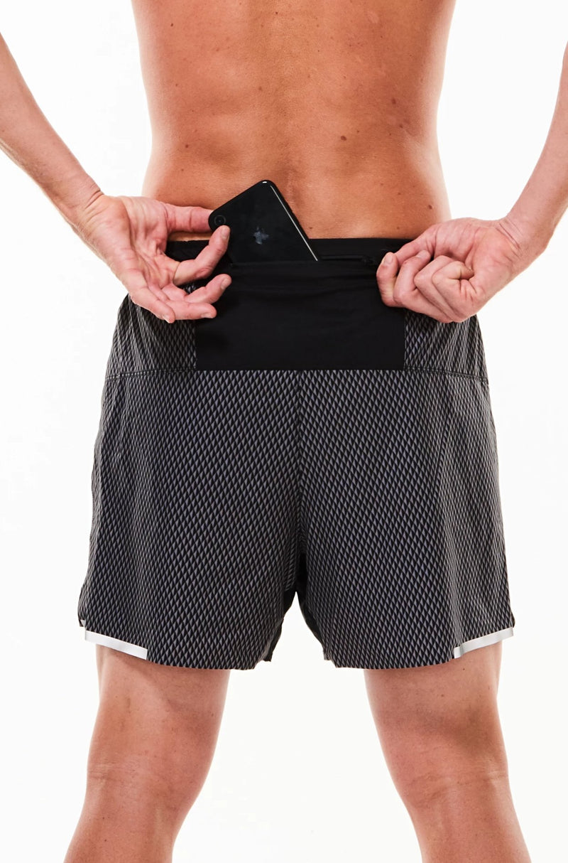 Model placing phone in back pocket of Black Reflect Noosa Run Short. Lined running shorts with pockets