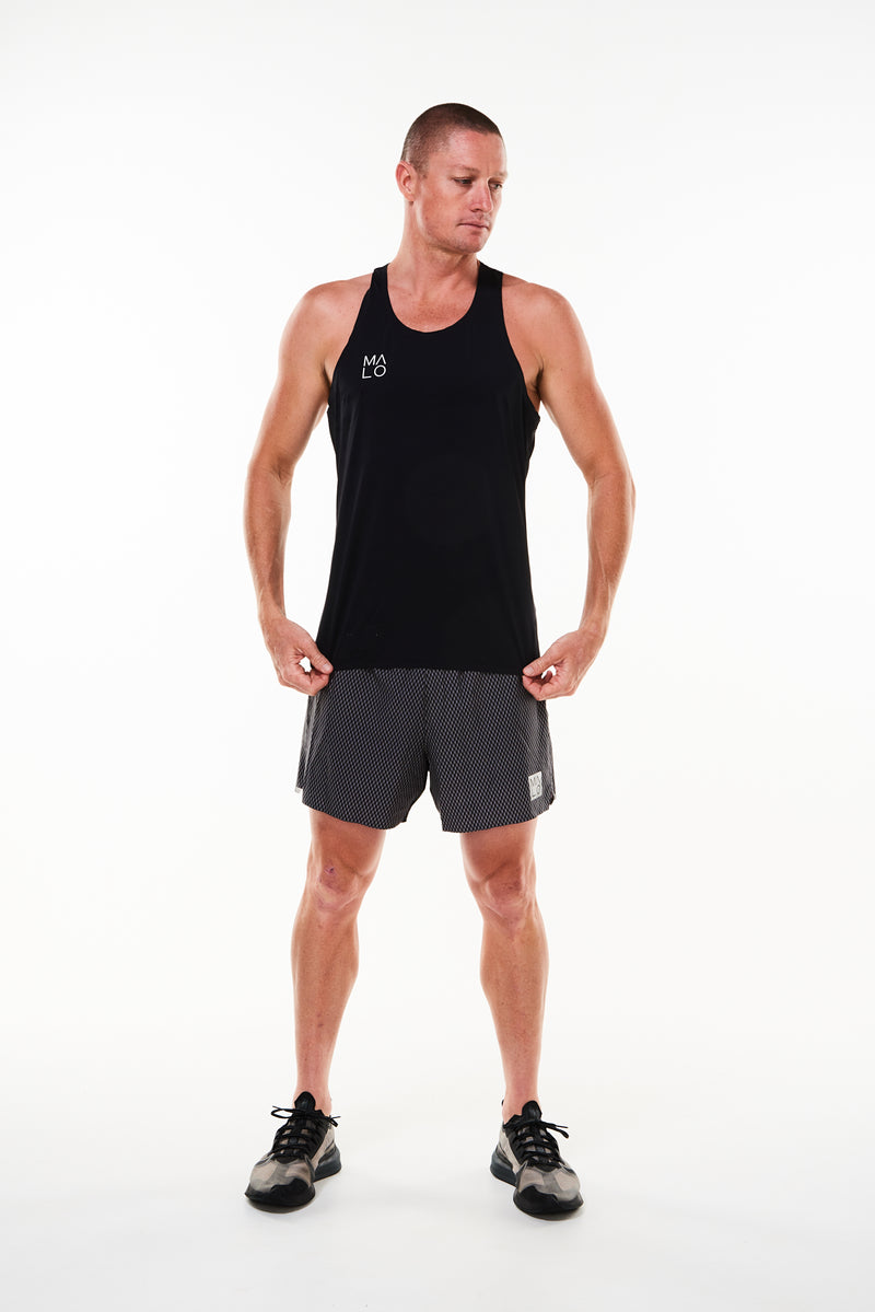 Model wearing men's Noosa Run Short with black singlet. Mid-thigh black run shorts with mesh liner.