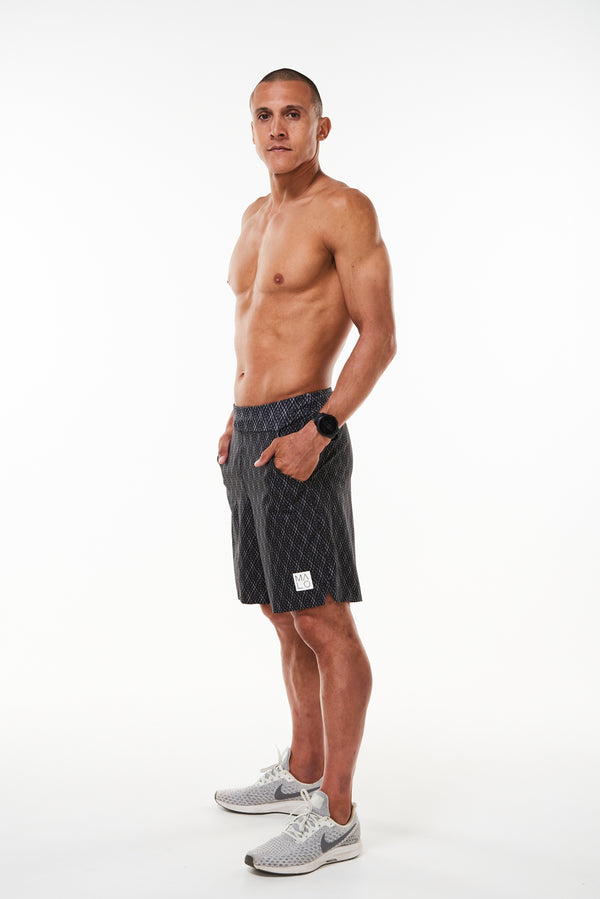 Left view model wearing Arvo Shorts with hands in pockets. Running shorts with reflective logo on left thigh.