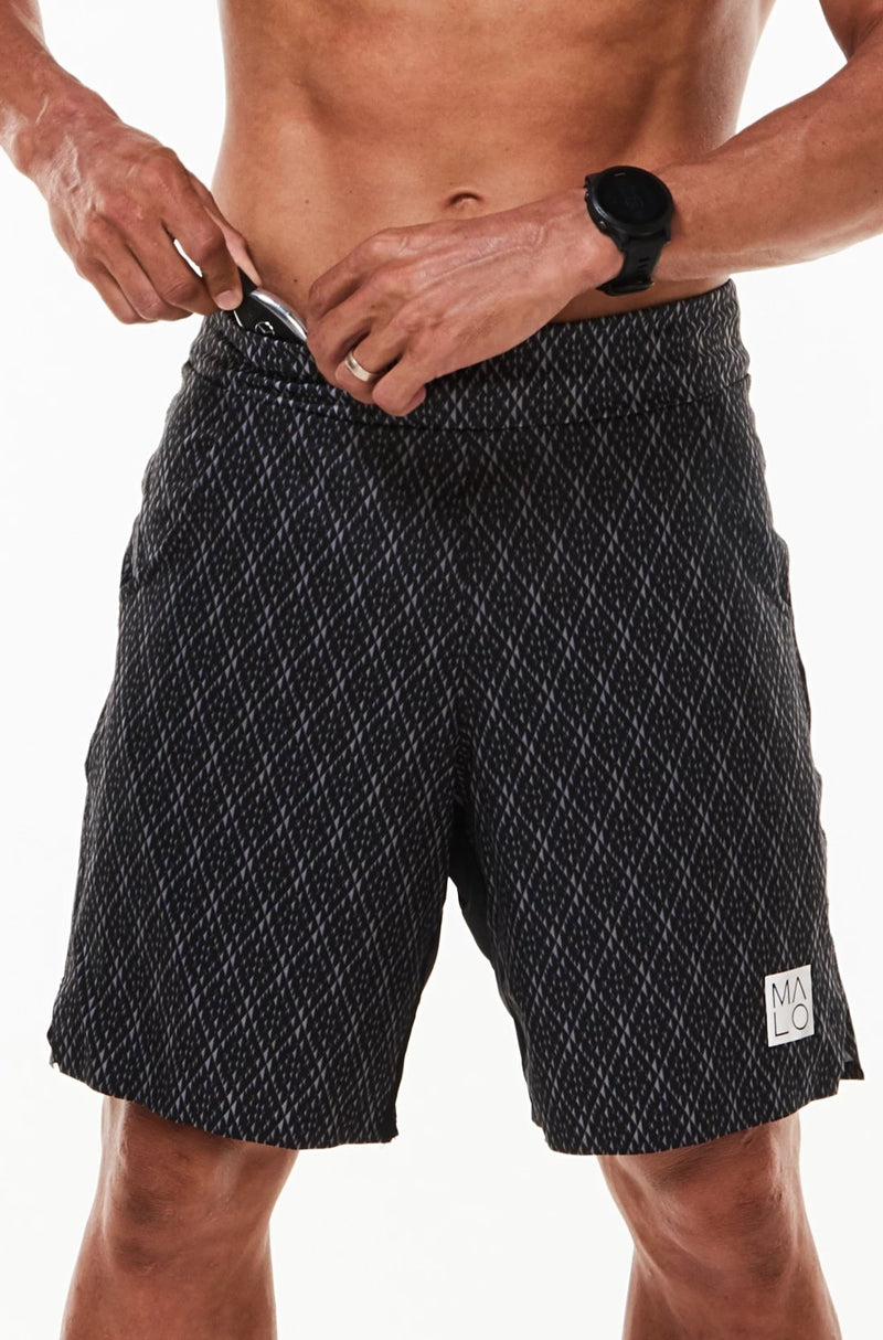 Model placing keys in small waistline pocket of Arvo Shorts. Black running shorts with pockets.