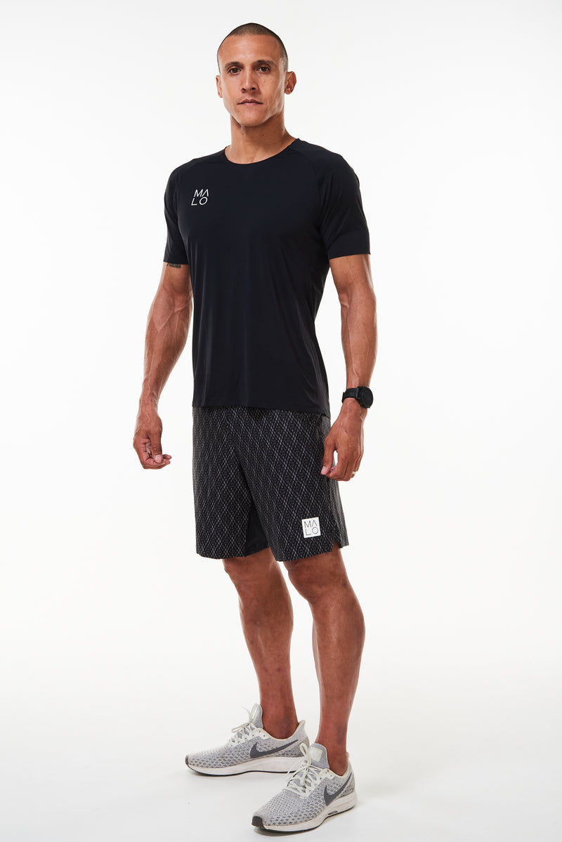 Model wearing Men's Edge Performance Tee. Black short sleeve t-shirt. Black workout shirt.