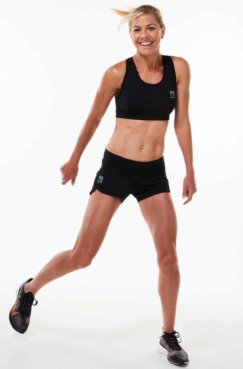 Model wearing Run The World Shorts with matching sports bra. Running shorts with low waistline.