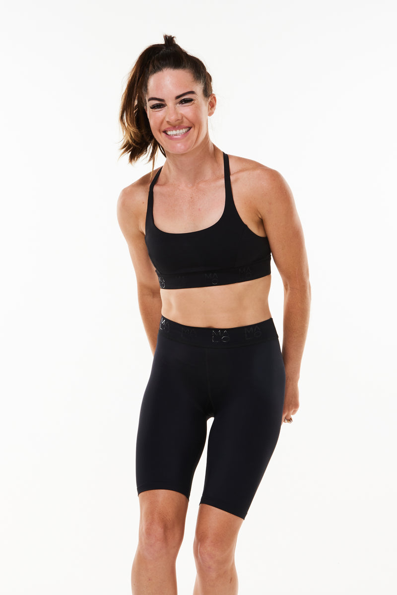 Model wearing black Bra with matching shorts. Performance sports bra to keep you cool and comfortable.