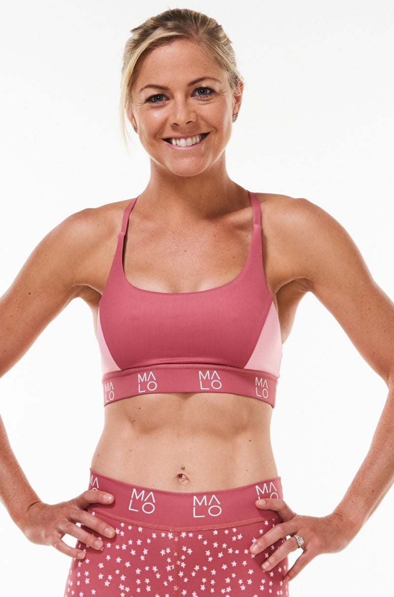 Model wearing pink Sunshine Bra with matching leggings. Performance sports bra to keep you cool and comfortable.