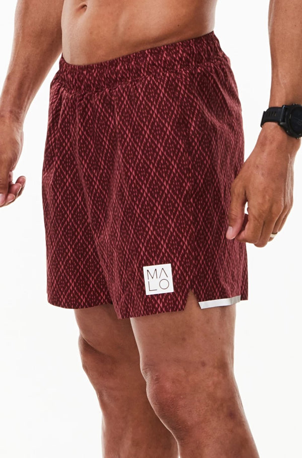 Left view men's Noosa Run Short. Mid-thigh red run shorts with reflective logo and stripe on left thigh.