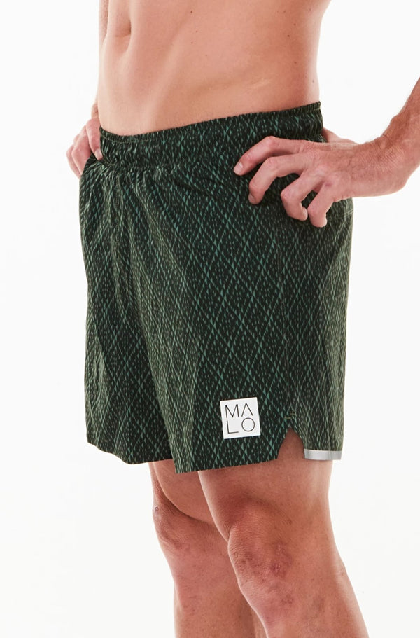 Left view men's Noosa Run Short. Mid-thigh green run shorts with reflective logo and stripe on left thigh.