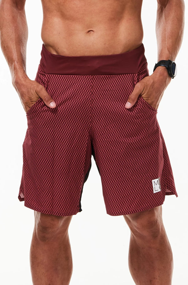 Model with hands in pockets of Arvo Shorts. Red workout shorts with pockets and comfortable waistline.