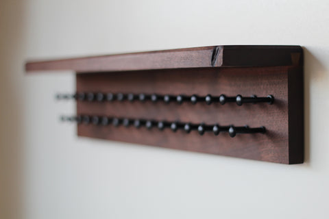 Walnut wood tie rack with shelf and black pegs