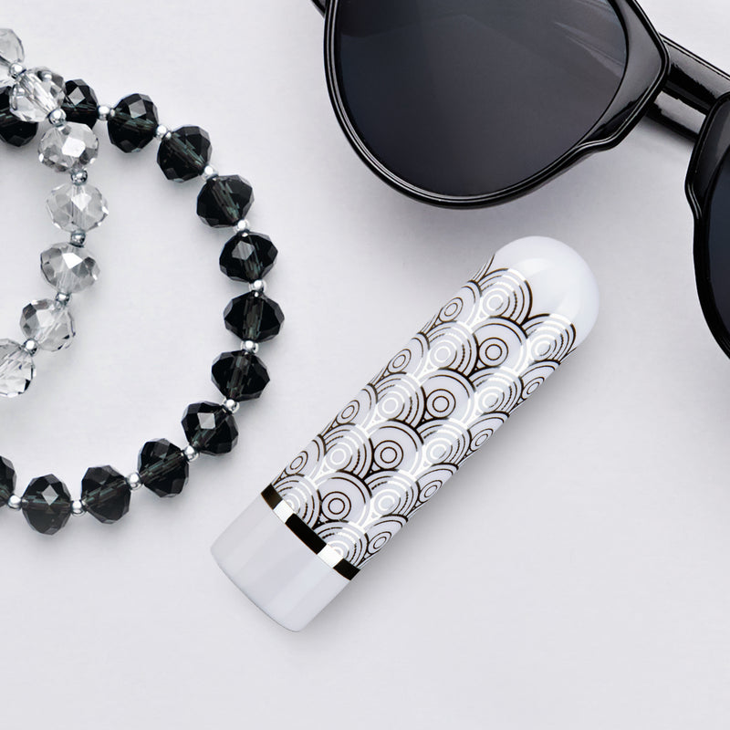 Blush Glitzy silver vibrator sitting on a table with jewelry and sunglasses for decoration | Kinkly Shop