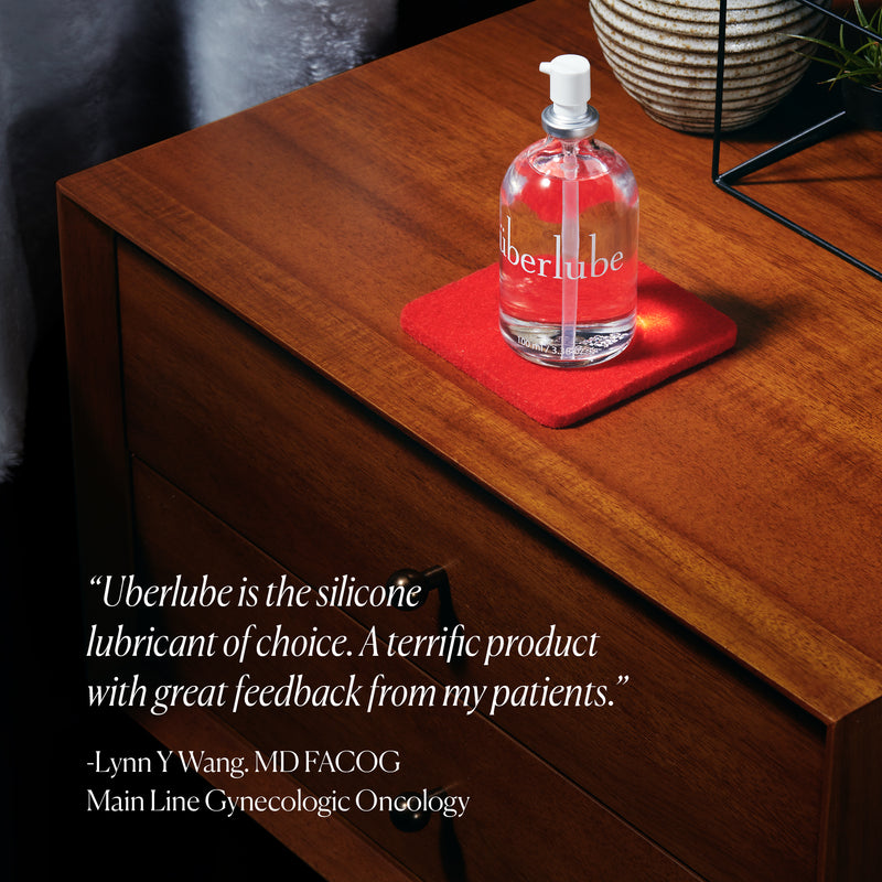 "Bottle of Überlube 100ml waterproof sex lube sits out on a nightstand on top of a vibrant red coaster. The quote on the image reads ""Uberlube is the silicone lubricant of choice. A terrific product with great feedback from my patients"" attributed to Lynn W. Wang at the Main Line Gynecologic Oncology department. 