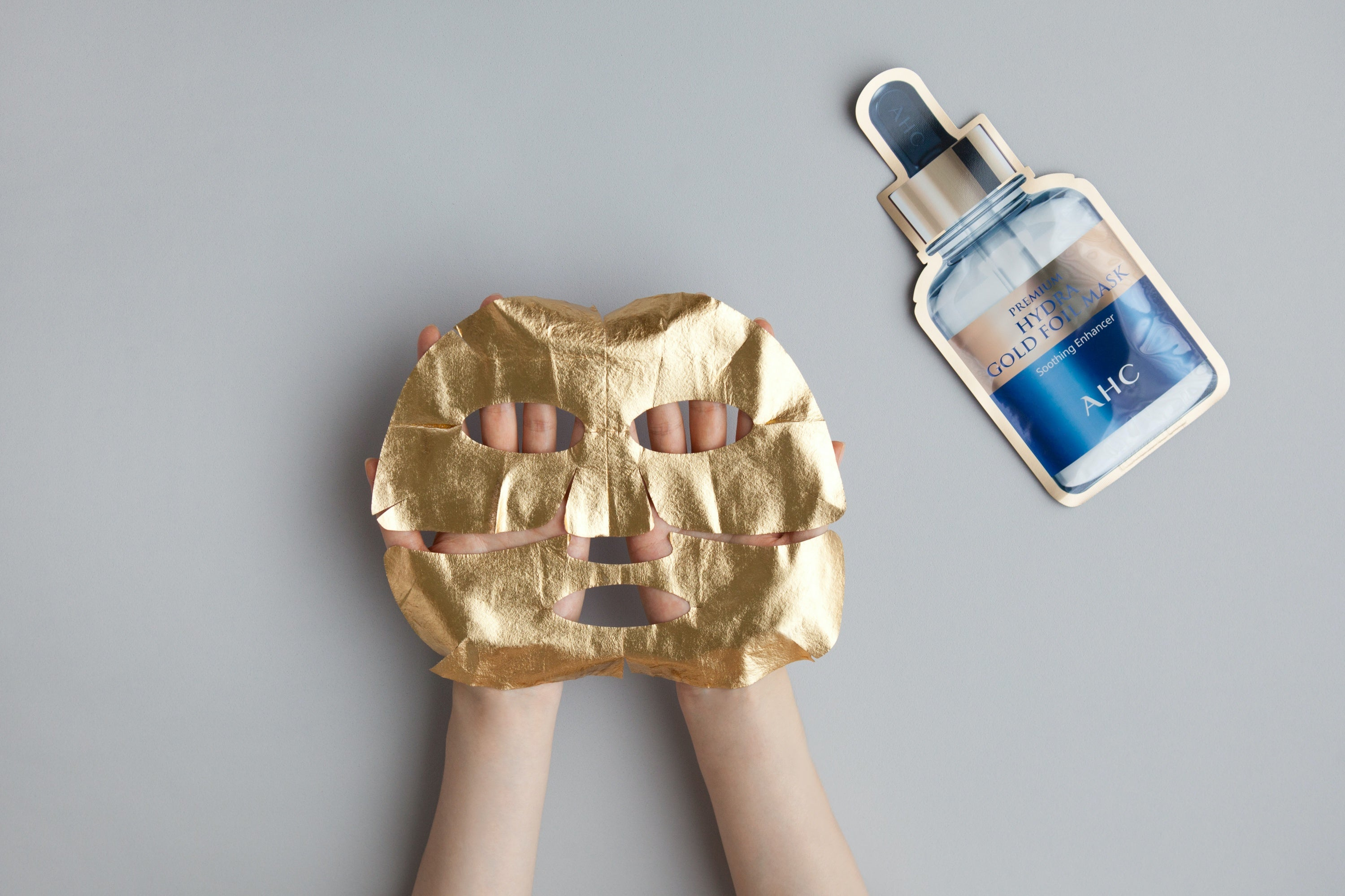 A hand holding AHC Premium Hydra Gold Foil Mask