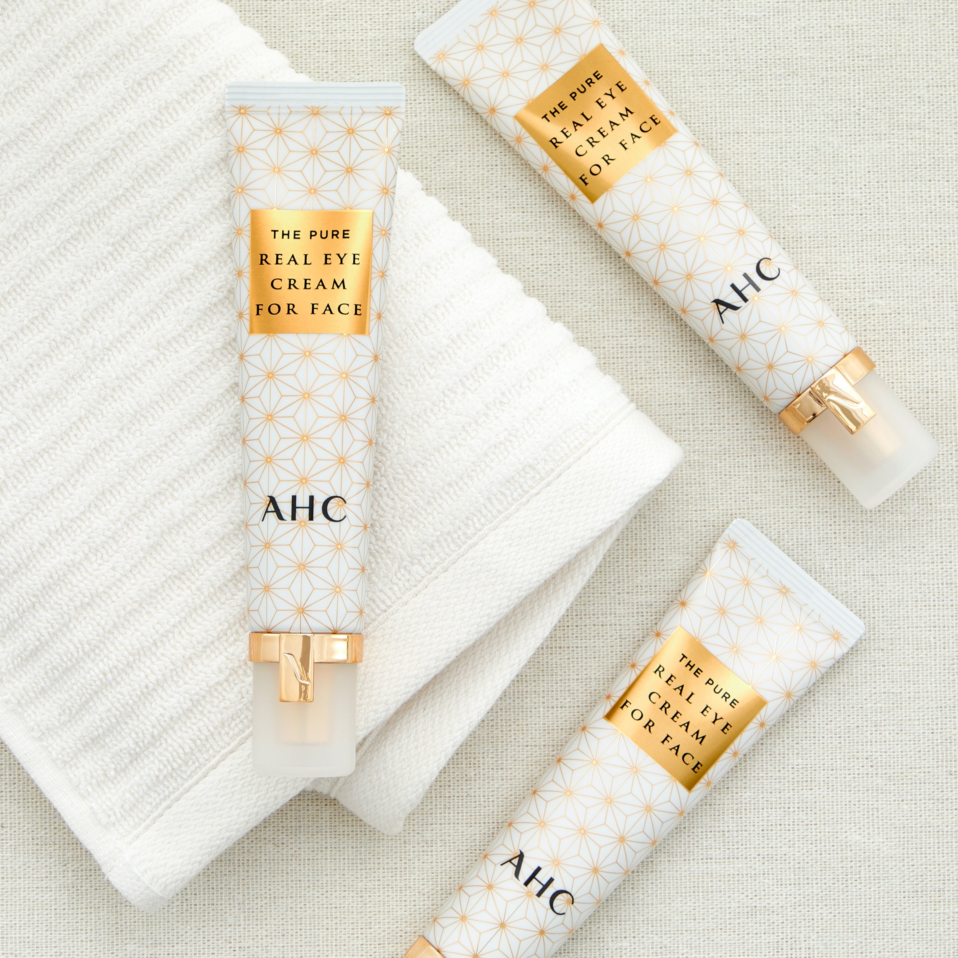 A packshot of AHC pure real eye cream for face on a gold background