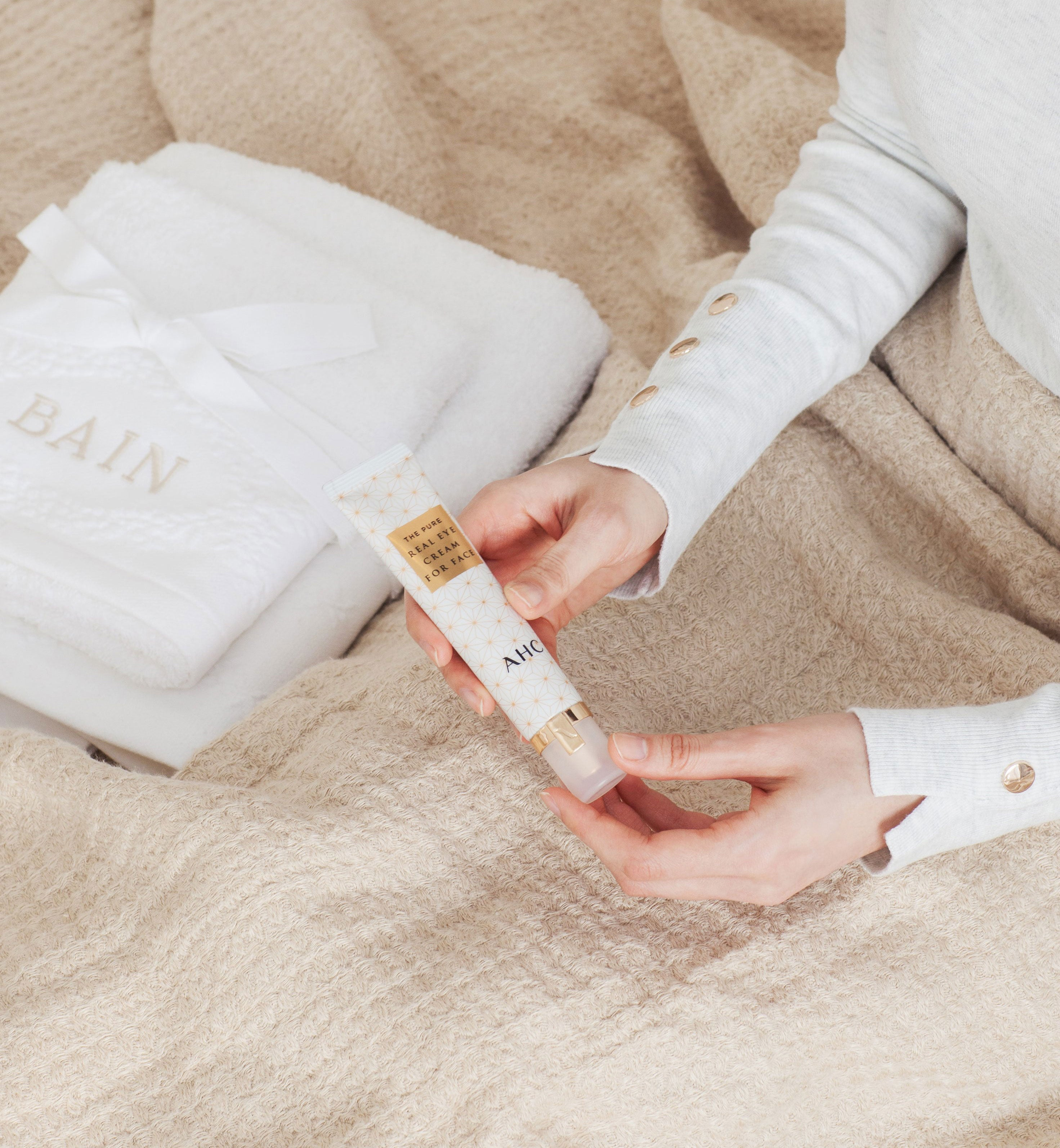 A hand holding AHC the pure real eye cream for face with a blanket background