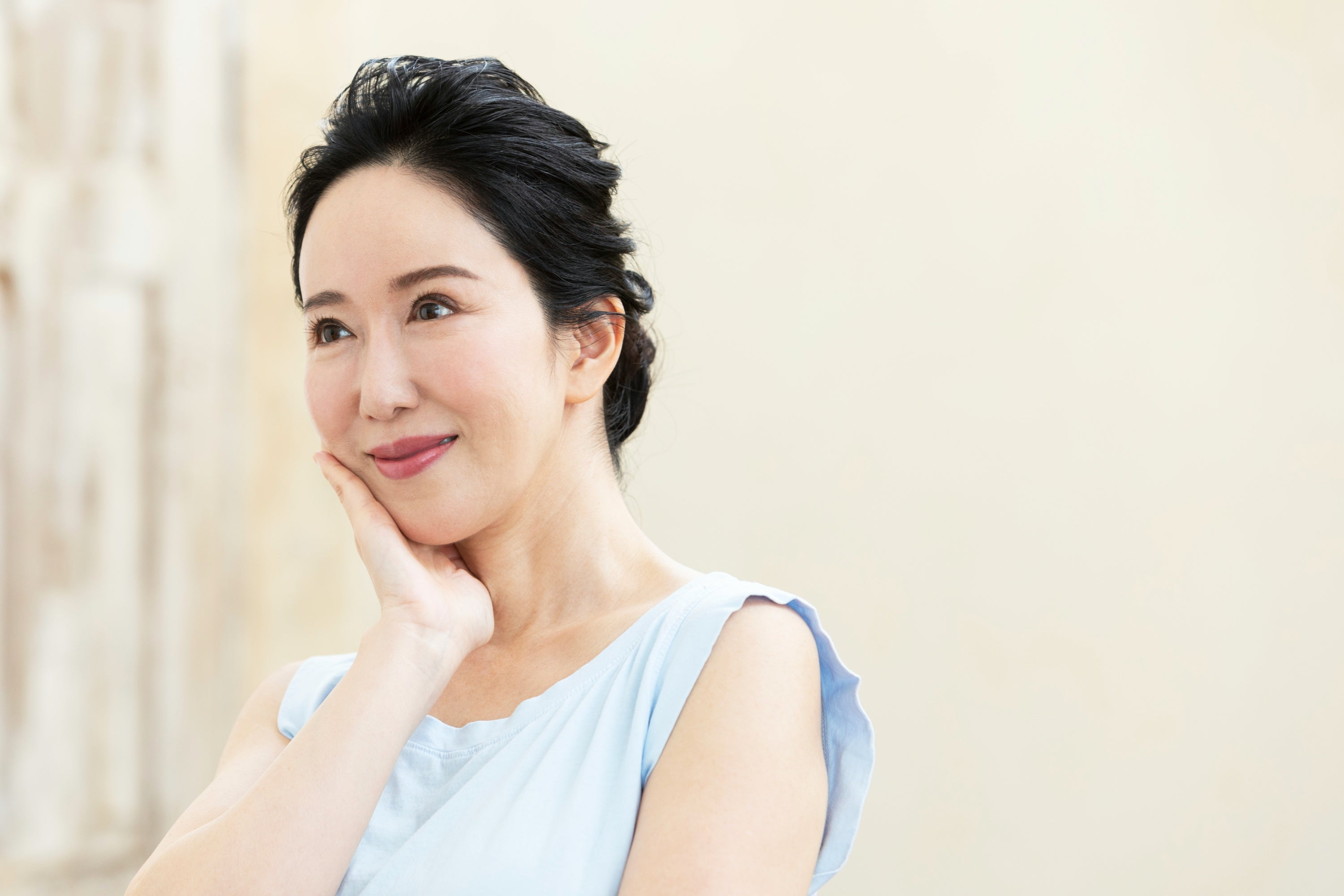 An Asian woman in her 40s with a nice skin touching her face