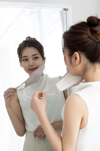 asian woman using mask and looking at the mirror