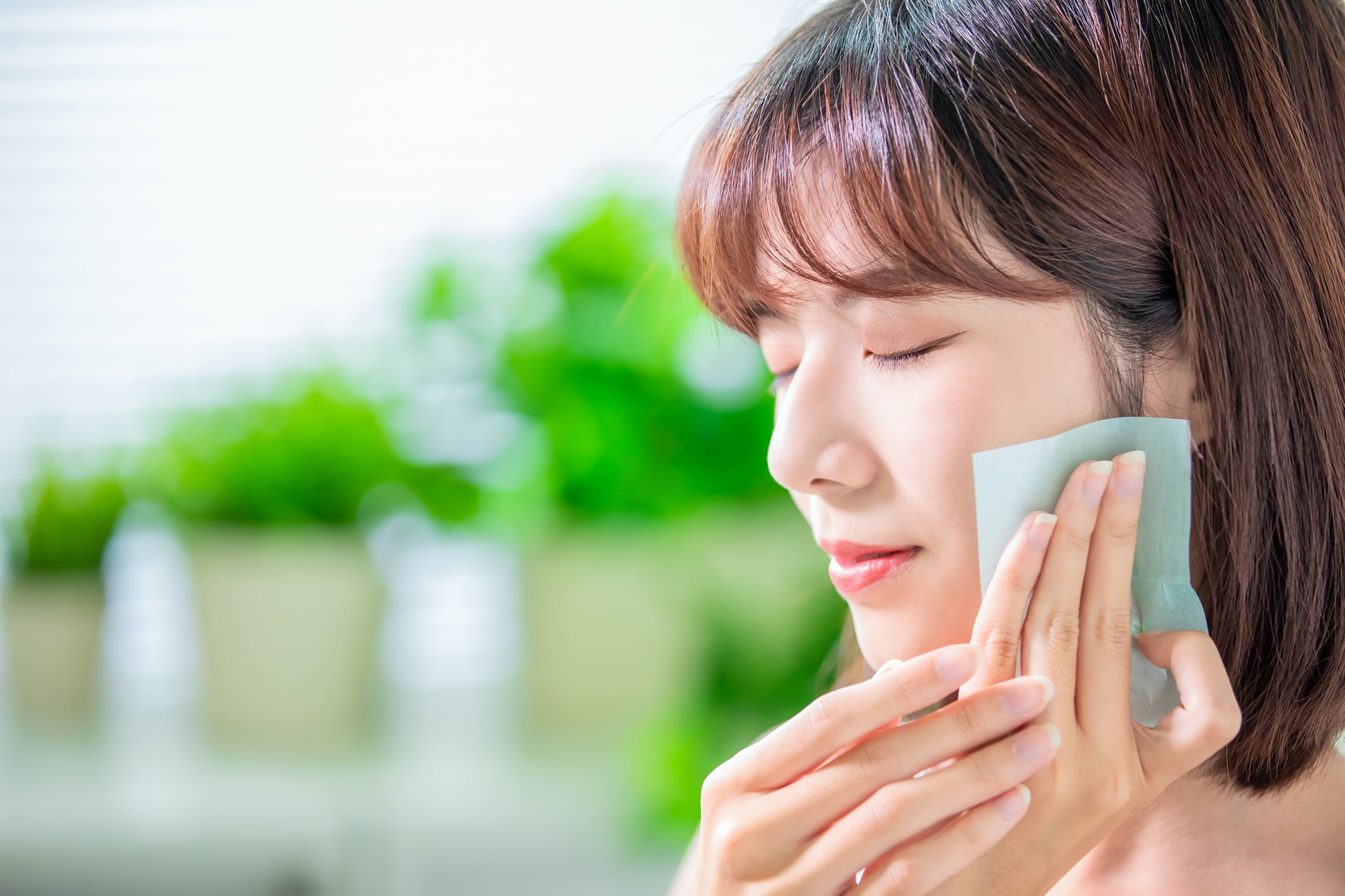 An Asian woman using toner for skin hydration