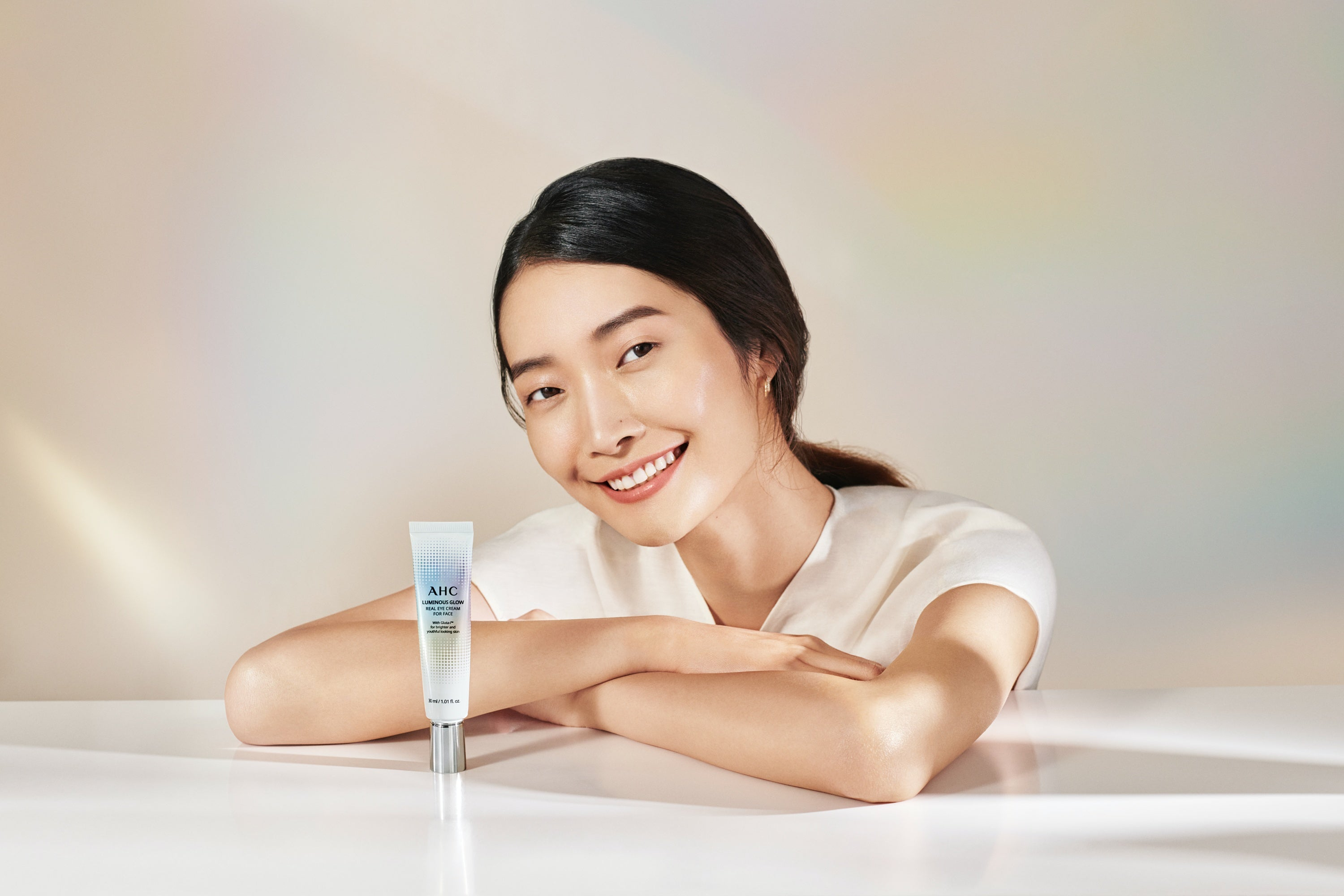 An Asian woman smiling and looking at the camera with AHC Luminous Glow Real Eye Cream for Face