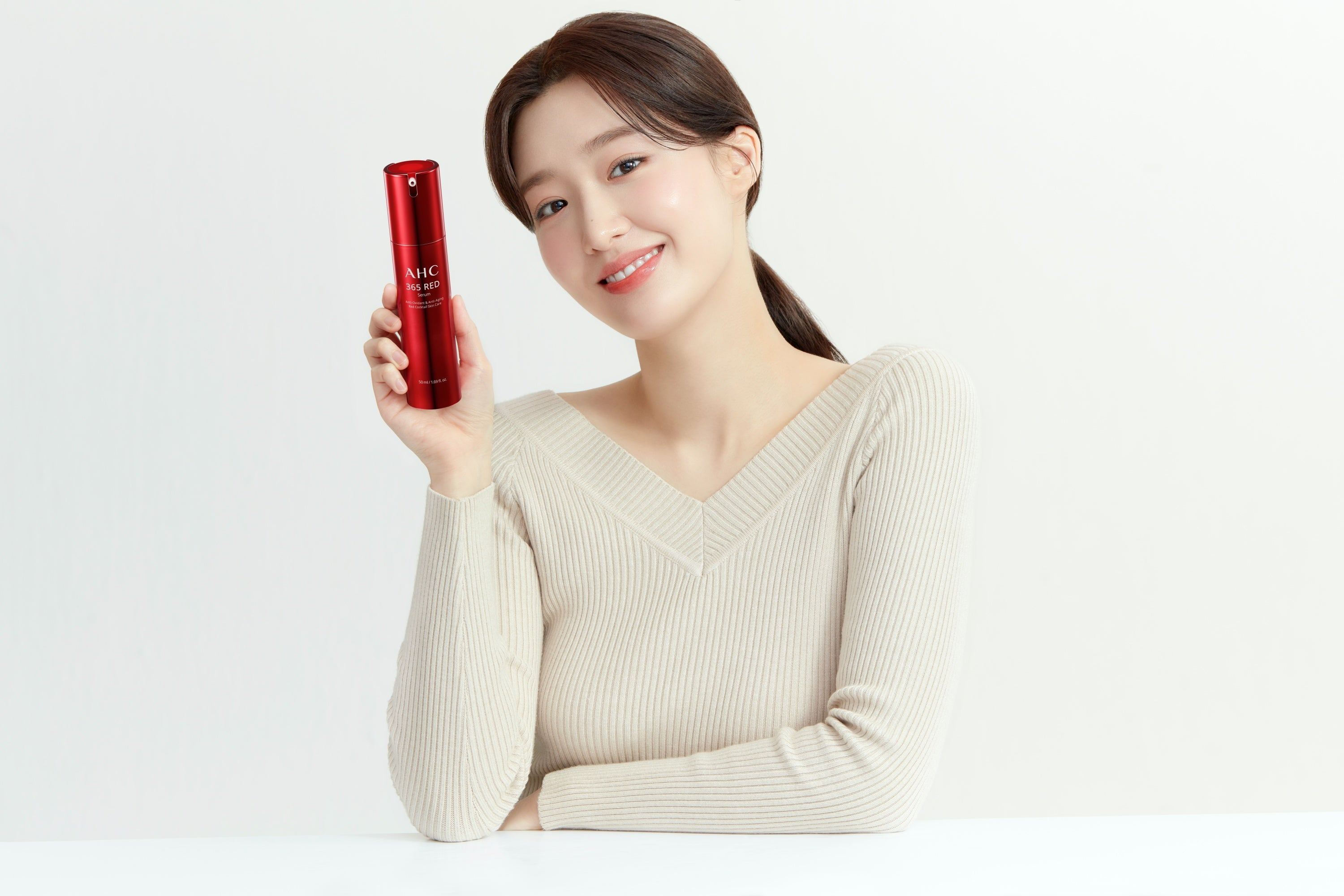 Cho Hye Joo holding a bottle of AHC red serum