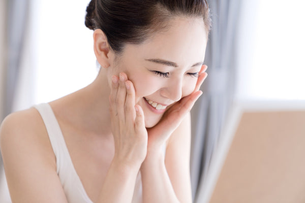 asian woman smiles and touch her cheek