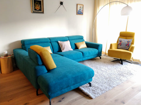 "Petrol blue couch, gold & ivory cushions, yellow chair with blue, dance motif cushion and a white rug describing ""Petrol Blue"" trend in home decor"